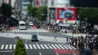 Wide shot first traffic then pedestrians cross an intersection in the Shibuya district of Tokyo taken with a tiltshift lens