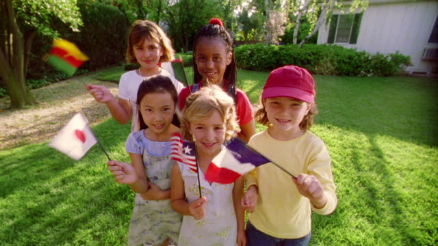 SELECTIVE FOCUS PORTRAIT wide shot five girls on lawn smiling + waving small various international flags
