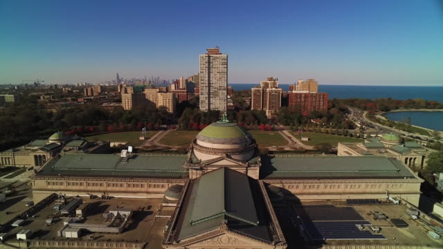 Wide shot flying north over Chicago Museum of Science and Industry on bright autumn day