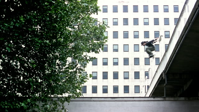 Wide shot freerunners jumping off ledge and rolling on roof