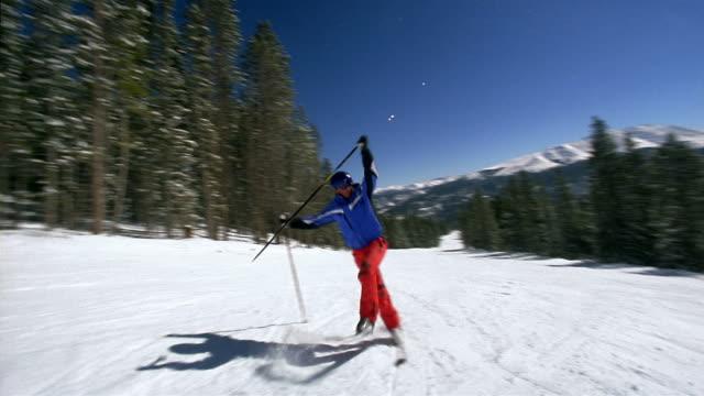 Wide shot freestyle skier doing one-handed pole flip / skating down slope / doing front flips on poles
