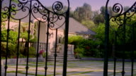 Wide shot gates opening in front of house