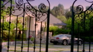 Wide shot gates opening to reveal Ferrari parked in front of mansion