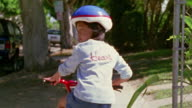 Wide shot girl riding bike with training wheels on sidewalk away from camera / California