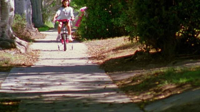 Wide shot girl riding bike with training wheels on sidewalk towards camera / California
