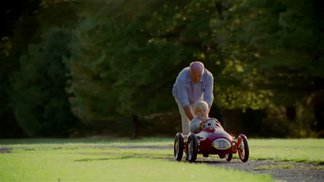 Wide shot grandfather pushing grandson in toy car on gravel pathway