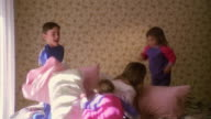 Wide shot group of children having pillow fight on bed