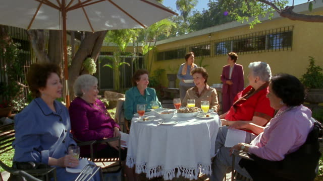 Wide shot group of senior women sharing meal on patio