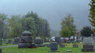 Wide shot hearse leading funeral procession on road in cemetery / Vermont