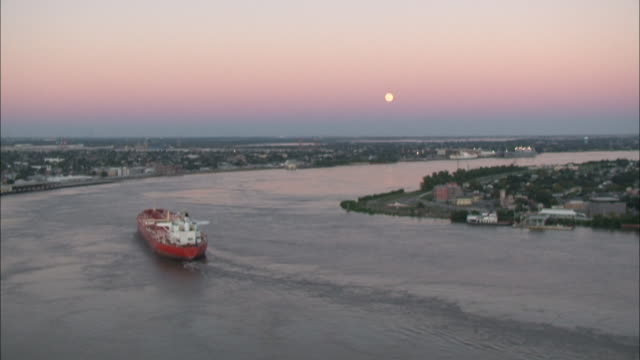 Wide Shot High Angle - Boat glides down calm river near town at dusk / New Orleans Louisiana