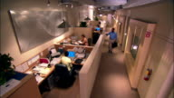 Wide shot - high angle Businesspeople waving goodbye and leaving office while man works late in cubicle