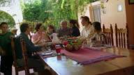 Wide shot Hispanic family eating meal outdoors with grandchildren kissing grandparents / Tucson, Arizona