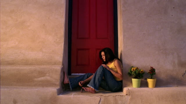 Wide shot Hispanic teenage girl sitting in doorway and painting toenails / Tucson, Arizona
