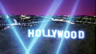 Wide shot Hollywood sign with spotlights and lights of San Fernando Valley in background at night / California