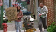 Wide shot homeless man with sign that says 'Whats the best nation in the world?' / other homeless man passing