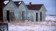 Wide shot 'House For Sale' sign w/dilapidated houses in background / WY