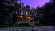 wide shot house + porch lights turning on + off in suburban house with fence at dusk