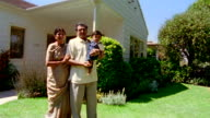 Wide shot Indian family standing in yard with house in background / California