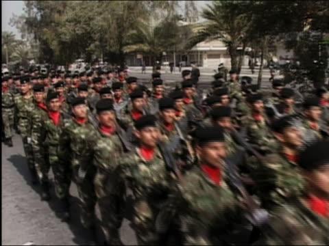 2003 wide shot Iraqi police in military uniforms marching in prewar Baghdad Iraq / AUDIO