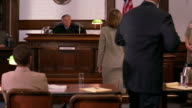 Wide shot judge requesting lawyers approach bench / judge talking to lawyers