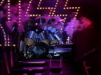 1982 wide shot Kiss drummer Eric Carr playing huge drum kit on rotating tank stage set / AUDIO