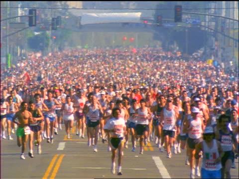 wide shot large crowd of people running in marathon toward camera on city street / Los Angeles Marathon