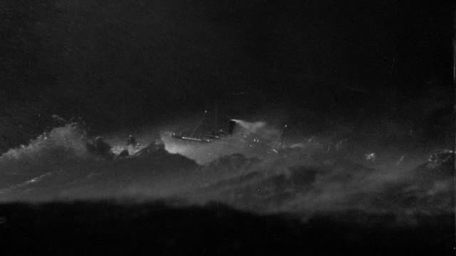 B/W wide shot large ship (model) in heavy storm + rough seas at night
