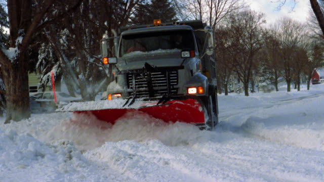 Wide shot large truck plowing snow on suburban street