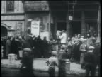 B/W 1932 wide shot line of people receiving free matzos from store / Lower East Side, NYC