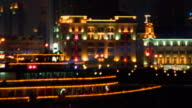 wide shot PAN lit up ferry passing buildings on riverbank with neon lights + spotlight / Shanghai, China