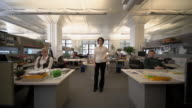 Wide shot lock down businesswoman standing in the middle of office, employees sitting at desks