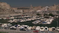Wide Shot Locked Down -  Marina full of pleasure-boatsT surrounded by the old city of Marseille / Marseille France