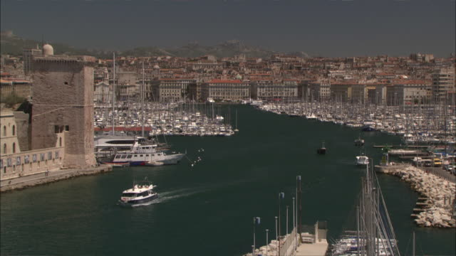 Wide Shot Locked Down -  The Old Port of Marseille, marinas full of pleasure-boats, Fort Saint-Jean and the old city in background / Marseille France