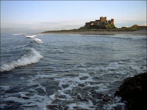 wide shot long shot Bamburgh Castle on hill with ocean waves breaking in foreground / Northumberland, England