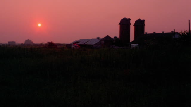Wide shot long shot time lapse sun setting behind farm buildings and silos / Tulsa, Oklahoma