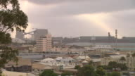 wide shot looking across Geraldton town to docks area / closer shot / pan housing to docks area / close up Australian flag flies on pole on top of...