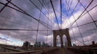 Wide shot low angle pan time lapse people walking on Brooklyn Bridge with suspension cables and clouds rolling over / NYC