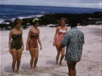 1953 Wide shot Male instructor teaching hula dancing to teenage girls and young woman on beach near ocean / Honolulu, Hawaii, USA