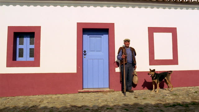 Wide shot man and German shepherd dog standing next to red + white house / Sao Pedro do Corval, Portugal