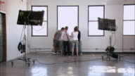 Wide shot man and woman prepare two men for photo shoot/ Brooklyn, New York