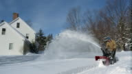 Wide shot man blowing snow off sidewalk in front of house / Vermont