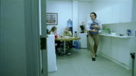 Wide shot man carrying water jug to cooler in office lounge / dropping jug and spilling water on floor