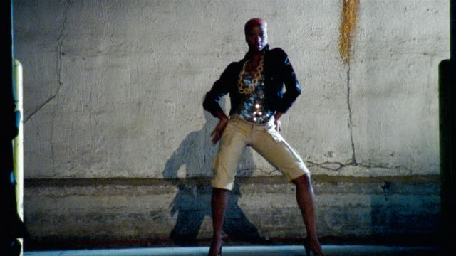 Wide shot man dancing against concrete wall and exiting/ woman entering and dancing