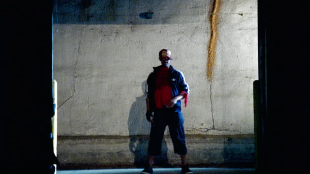 Wide shot man dancing against concrete wall/ woman entering and dancing with man