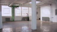 Wide shot man entering empty loft space, setting down bicycle, walking and looking around/ Brooklyn, New York