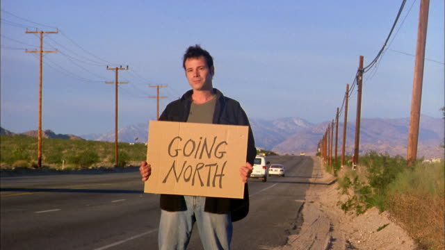 Wide shot man hitchhiking by desert highway holding 'Going North' sign