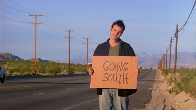 Wide shot man hitchhiking by desert highway holding 'Going South' sign