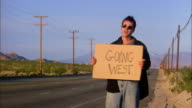 Wide shot man hitchhiking by highway holding cardboard 'Going West' sign