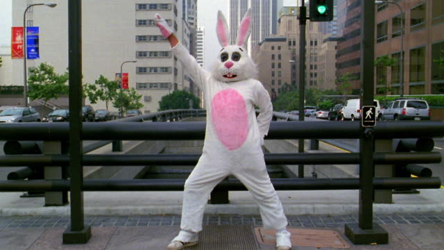 Wide shot man in rabbit costume striking disco pose with office buildings in background / Los Angeles, CA