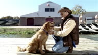 Wide shot man kneeling on the ground and petting and scratching golden retriever